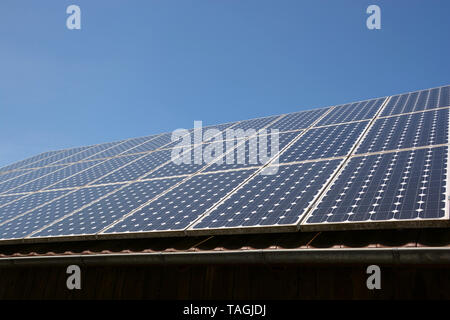 solar panel on roof and sky background, modern solar cells or photovoltaic on the roof of an old woodshed with new gutter in front of azure sky - Stock Image
