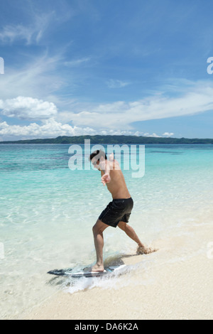 A man playing on a surfboard. - Stock Image