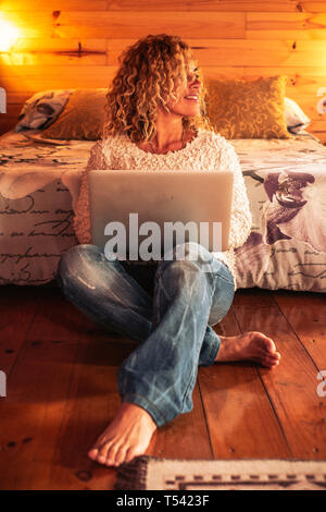 People using technology at home - happy beautiful caucasian woman with laptop on the legs sitting in the bedroom - home or hotel place and warm sweet  - Stock Image