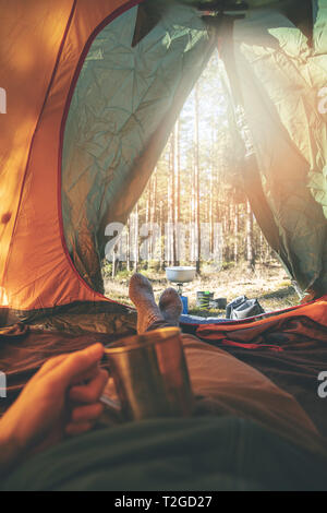 wanderlust - man relaxing in tent after hike with cup of tea - Stock Image