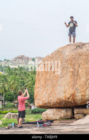 Tourists rock climbing in Hampi, India. - Stock Image