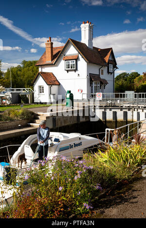 England, Berkshire, Goring on Thames, lock keepers cottage at locks on River Thames, as leisure boat passes through - Stock Image