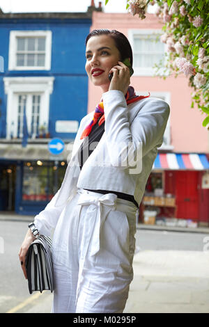 Woman in white linen culotte suit using phone in street - Stock Image