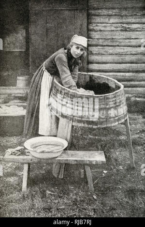 Young housewife at work, doing the laundry in a three-legged washtub, Republic of Estonia. - Stock Image