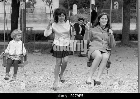 young girl sitting on a swing looks on as two adult women play on swings next to her 1970s hungary - Stock Image