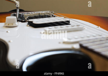 Looking  over the bridge, scratch plate and vibrato arm of an electric guitar. - Stock Image