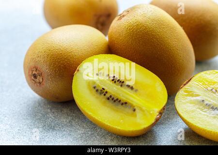 Golden (yellow) organic kiwi. Whole and cut ripe juicy fruits on grey background. kiwifruit.  Actinidia chinensis. Selective focus - Stock Image