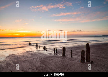 Remains of groynes on the beach at Sandsend, Whitby, North Yorkshire, at dawn - Stock Image