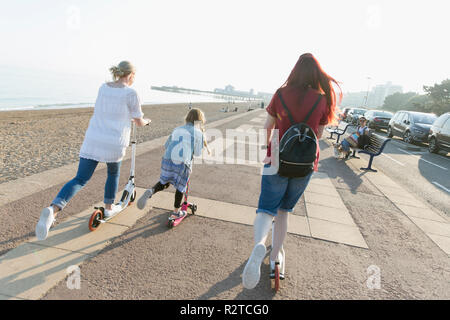 Lesbian couple with daughter riding push scoters on sunny beach boardwalk - Stock Image