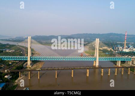 (190423) -- CHONGQING, April 23, 2019 (Xinhua) -- Aerial photo shows the last train running on the previous Baishatuo Yangtze River railway bridge (Front) in Jiangjin of southwest China's Chongqing Municipality, on April 23, 2019. The previous Baishatuo Yangtze River railway bridge, completed in 1959, will stop service after April 24. All trains will run on the new double decker steel truss cable stay railway bridge after that day. The new bridge has 4 tracks on the upper deck for passenger trains with a designed speed of 200 kilometers per hour and 2 tracks on the lower deck for cargo trains  - Stock Image