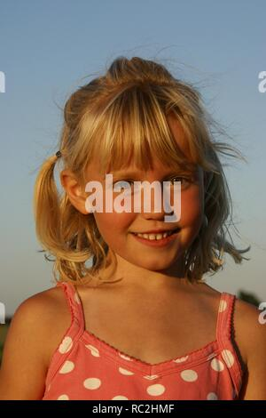 Cute happy young girl outside against blue sky, look at camera, blonde Dutch girl, with hair worn in tails - Stock Image