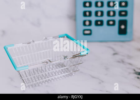 empty shopping basket and huge calculator in the background, concept of shopping budget - Stock Image
