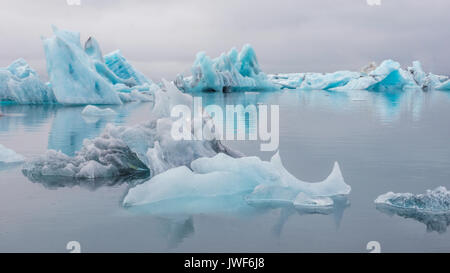 Group of turquoise colored icebergs and reflections in the still water of Jokulsarlon glacier lagoon. Iceland. - Stock Image