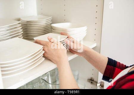 Woman puts clean dishes on the shelf in kitchen cupboard. - Stock Image