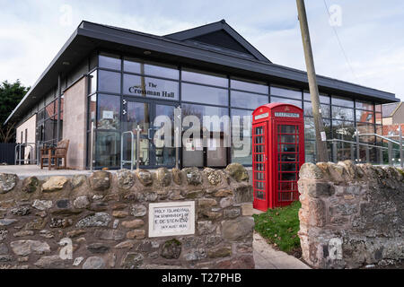 Lindisfarne or Holy Island, Northumberland coast south of Berwick-on-Tweed, England. The Crossman Hall and a red telephone box. - Stock Image