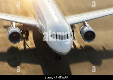 Detail of commercial jetliner forcing on runway. Motion blur effect added. Shot from high angle - Stock Image