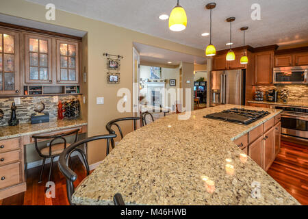 An upscale kitchen with granite slab countertops, hardwood flooring, stainless appliances and extra large center - Stock Image