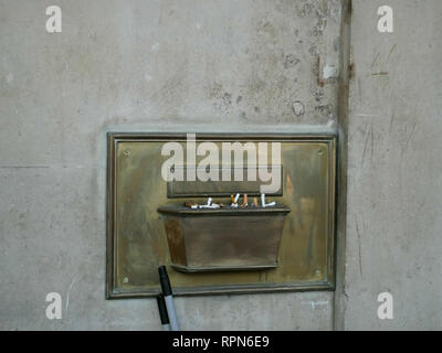 Brass ashtray attached to the wall filled with cigarettes - Stock Image