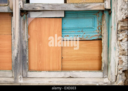 A window boarded up by wooden panels in an old house - Stock Image