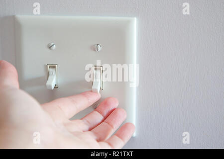Hand about to turn a light switch from the off position to on - Stock Image