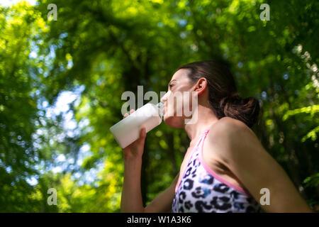 sportswoman drinking water from a glass bottle - Stock Image