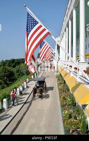 Horse drawn carriage shuttling guests to the Historic Grand Hotel on resort island (and state park) of Mackinac Island, Michigan, USA. - Stock Image