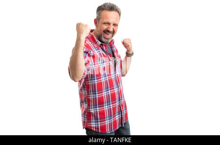 Cheerful male person celebrating success by making happy gesture with fists up isolated on white - Stock Image