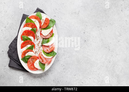 Delicious italian caprese salad with ripe tomatoes, fresh garden basil and mozzarella cheese. Top view flat lay with copy space - Stock Image