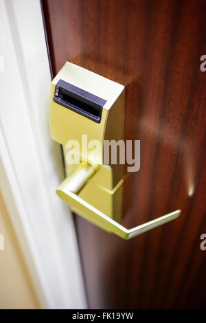Hotel room brass electronic door lock and handle on a wood door - Stock Image