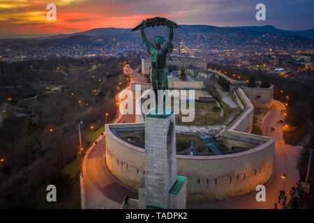 Budapest, Hungary - Aerial view of the Hungarian Statue of Liberty with Buda Hills and amazing colorful sunset behind at winter time - Stock Image