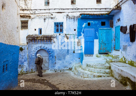 Chefchaouen, Morocco : A Moroccan woman walks past blue-washed traditional buildings in the medina old town. - Stock Image