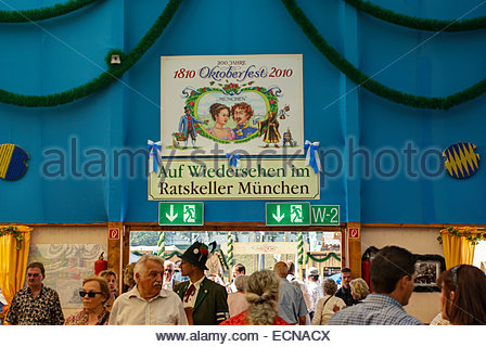 Visitors to Oktoberfest walk beneath sign commemorating marriage of King Ludwig I to Therese of Saxe-Hildburghausen - Stock Image