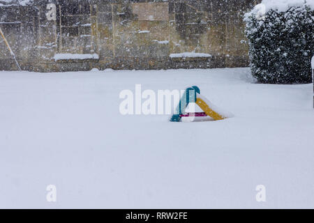 An empty mini baby slide is alone in a snowy garden - Stock Image
