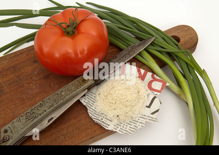 Tomato, salt on the newspaper, old knife and onions on a board - Stock Image