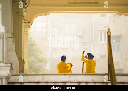 Two security guards wearing a dastar are talking in front of the Harmandir Sahib (Golden Temple) Amritsar, Punjab, India. - Stock Image