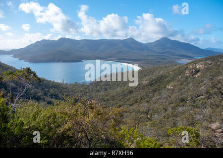 Wineglass Bay, Freycinet National Park, Tasmania seen from the lookout track on a summer day with blue sky and clouds - Stock Image