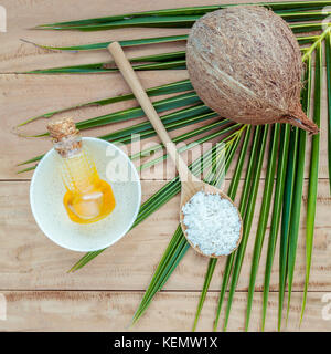 Coconut oil , coconut powder and coconut on coconut leaves set up on brown wooden background for alternative therapy. - Stock Image