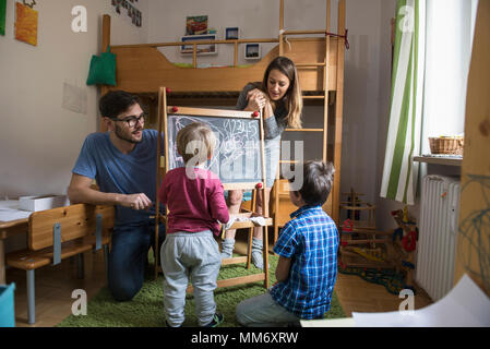 Little boy is writing on a blackboard, parents and the older brother are watching, Munich, Germany - Stock Image