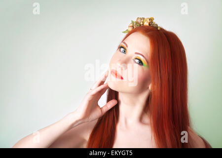 Portrait of beautiful red-haired girl with flowers in her hair and bright makeup - Stock Image