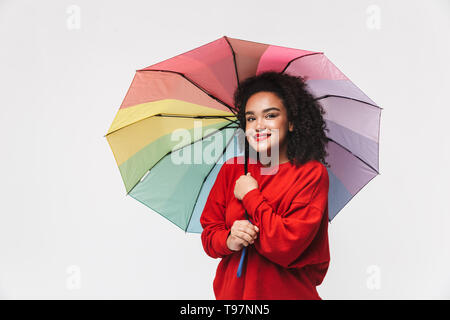 Portrait of a cheerful african woman standing isolated over white background, holding colorful umbrella - Stock Image
