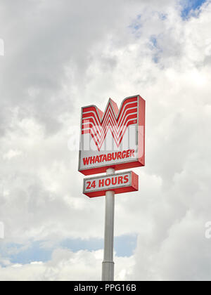 Whataburger fast food restaurant exterior sign and corporate logo on tall sign poll indicating 24 hours service near the Interstate in Alabama USA. - Stock Image
