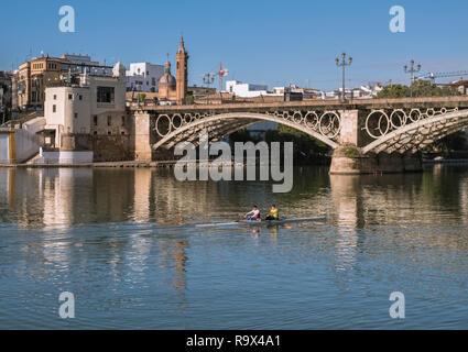 Isabel II bridge, better known as Puente de Triana bridge, as it crosses the Guadalquivir river, Triana District, Seville, Spain - Stock Image