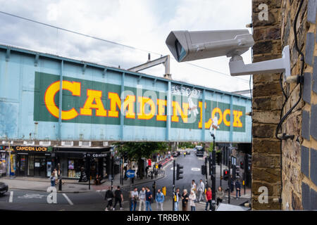 Security CCTV camera overlooking Camden Marketplace and Iconic painted Camden Lock sign on side of railway bridge in London with street and people in - Stock Image