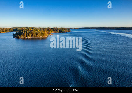 Some of the 30,000 islands of the Stockholm Archipelago, viewed from the deck of a cruise liner approaching the port, just after sunrise. - Stock Image