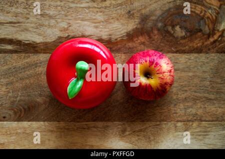 Two red apples, fake and real against a wooden background. - Stock Image
