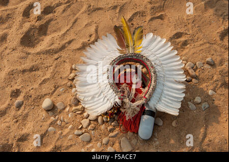 A white feather cokaa headdress lies on the ground with the owner's iPhone speaker at the International Indigenous - Stock Image
