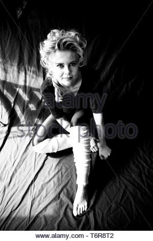 Tilburg, Netherlands. Studio portrait of a young adult, blonde, female dancer, against a black background cloth. Shot on Analog Black & White film in  - Stock Image