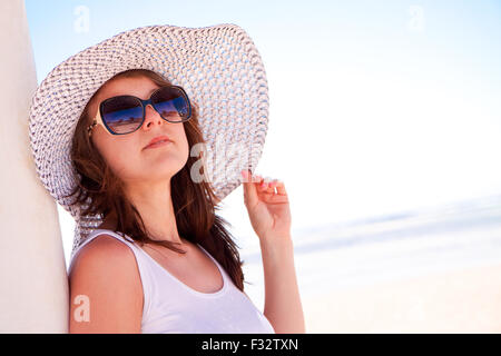 A young white girl in a hat on the beach - Stock Image