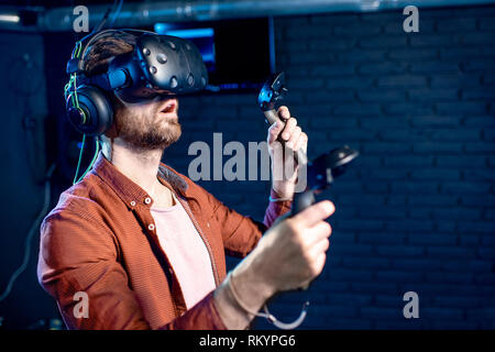 Man playing game using virtual reality headset and gamepads in the dark room of the playing club - Stock Image