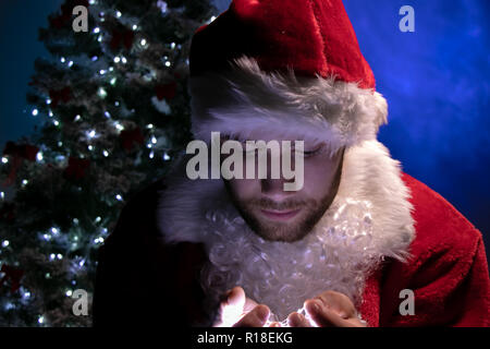 Good looking male santa looking down at lights in his hands in front of christmas tree - Stock Image